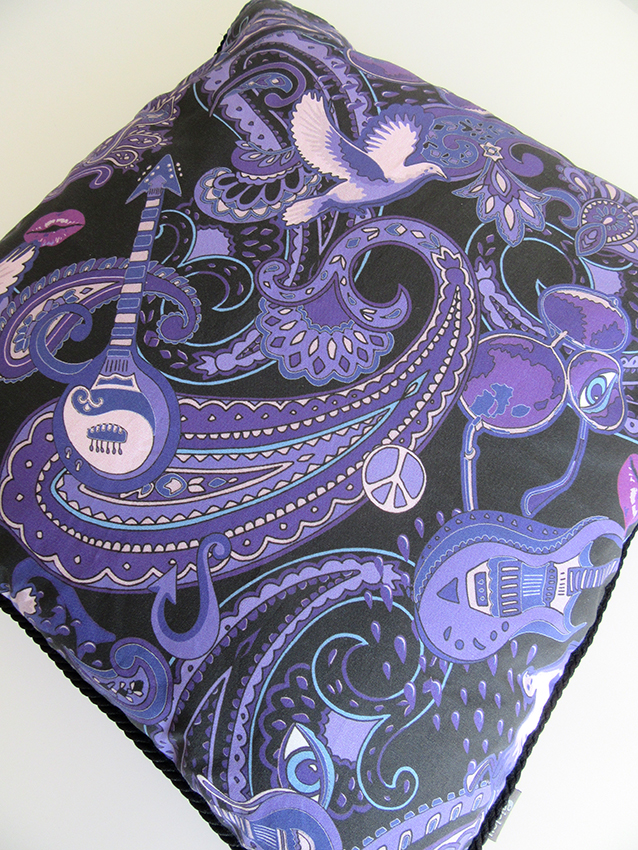 Paisley Prince Songbook cushion designed by Patrick Moriarty. The purple cushion has luxurious black rope piping sewn along the edges of the cushion to separate the fancy Prince artwork on the front and the bright purple cotton on the back.
