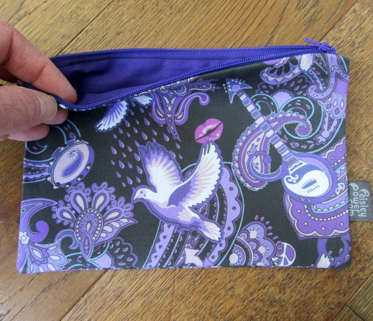 zip bag with motifs symbolizing the songs of Prince Rogers Nelson. Each bag has a purple zip and bright purple lining.