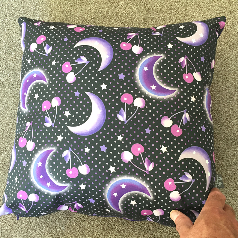 Pillow cover made with the large black version of the Cherry Moon printed fabric