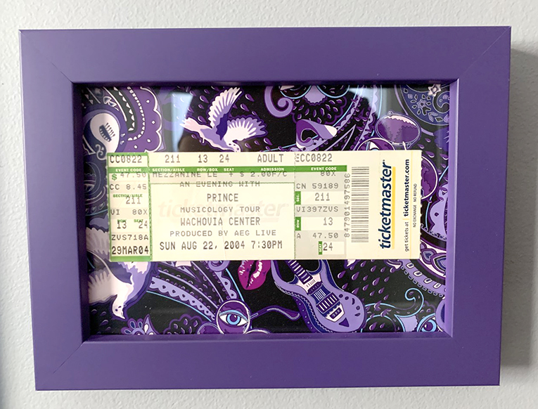 Prince live concert ticket memorabilia.  There is card printed with the Paisley Prince Songbook pattern in the background of the frame