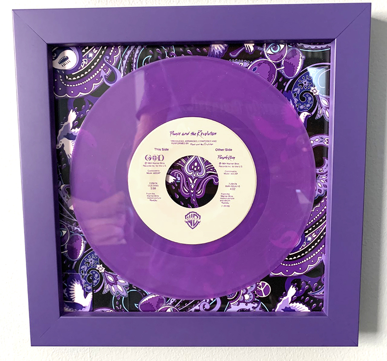 purple rain vinyl disk framed memorabilia. Paisley Prince Songbook pattern in the background of the frame.