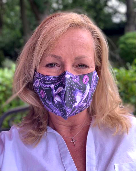 Jeannie Gilding in Cheshire modeling a Paisley Prince Songbook face mask. the mask is 100% cotton.