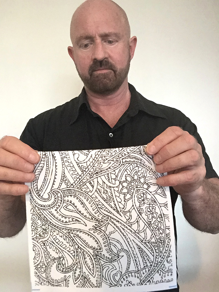 designer patrick moriarty holding paisley pattern fabric square