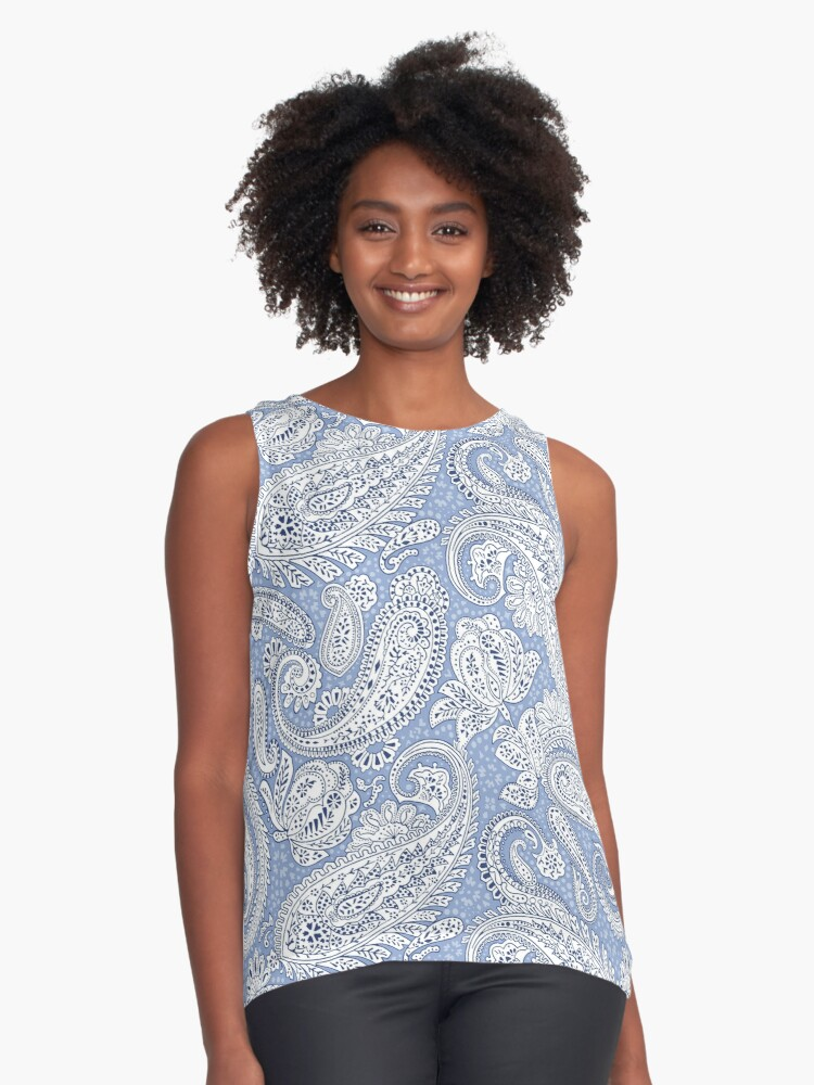 A model wearing a sleeveless top printed with the light blue version of the Paisley Positivity design
