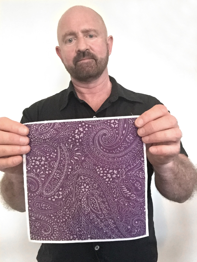 designer Patrick Moriarty holding a test sample of Paisley Positivity design (the small-scale aubergine version) printed on cotton